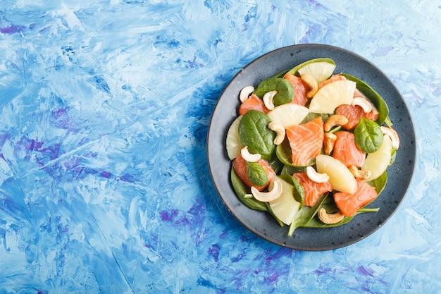 Salmão fresco com abacaxi, espinafre e caju na placa cerâmica em um concreto azul.