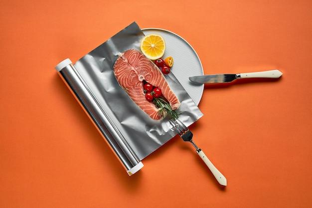 Salmão fresco com limão em papel alumínio, pronto para cozinhar no forno em fundo laranja.
