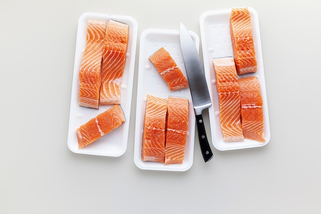 Salmão fresco, cortado em pedaços e pronto para cozinhar, e uma grande faca de chef. caixa de plástico