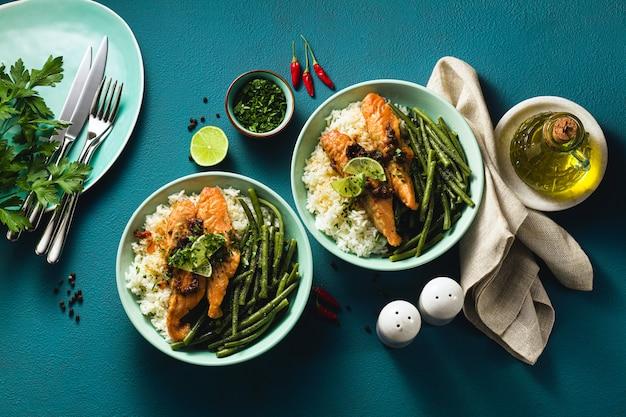 Salmão fresco frito com gengibre e alho no leite de coco, com arroz basmati e feijão verde em pratos na mesa. receita saudável para toda a família.