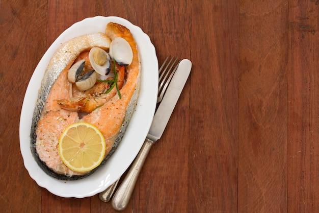 Salmão frito com frutos do mar e limão no prato branco