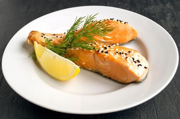 Salmão frito com gergelim, limão, endro em um prato branco. foco seletivo.