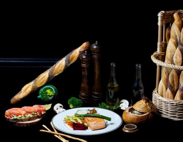 Salmão frito com legumes e sopa de cebola no pão