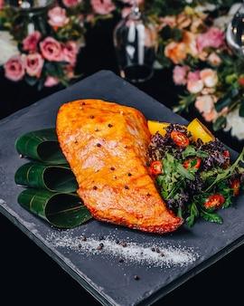 Salmão frito com legumes na mesa