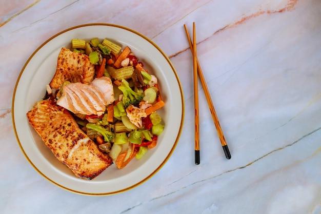 Salmão frito rosa com legumes asiáticos no prato com pauzinhos. vista do topo.