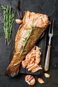 Salmão fumado a quente, carne de peixe truta. fundo preto. vista do topo.