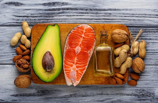 Salmão gordo saudável, abacate, óleo, nozes