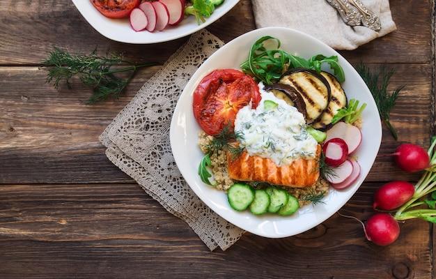 Salmão grelhado, berinjela e tomate com molho de quinua e tzatziki em madeira rústica. jantar saudável.