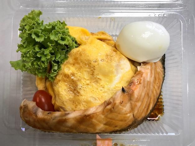 Salmão grelhado com arroz em omelete de ovo no recipiente de comida na mesa