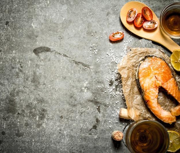 Salmão grelhado com azeite, tomate, limão e especiarias na mesa de pedra.