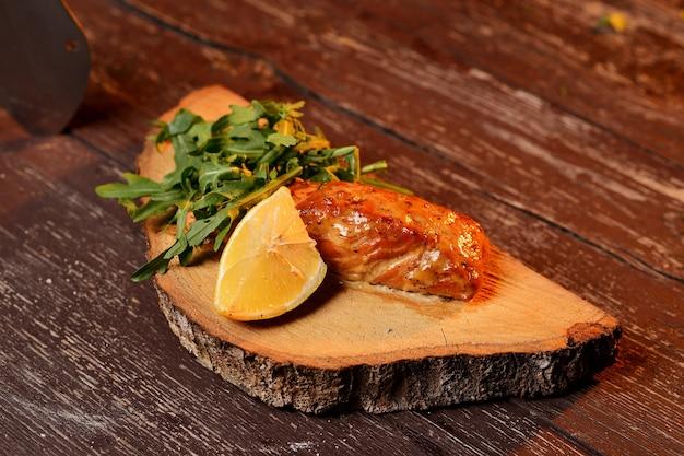 Salmão grelhado com limão e rúcula. em uma placa de madeira.