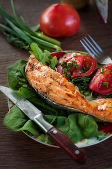 Salmão grelhado e salada na mesa de madeira.