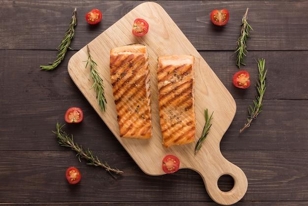 Salmão grelhado e tomate, alecrim na mesa de madeira