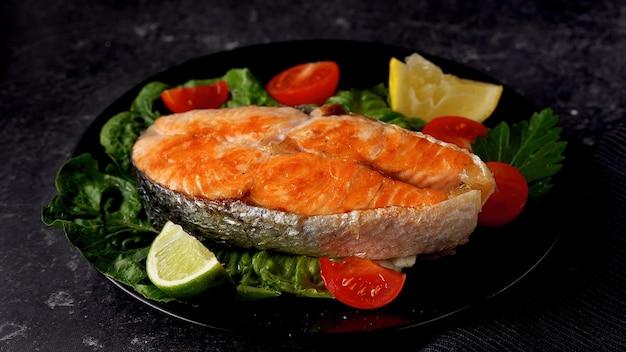 Salmão grelhado e vegetais, bife de salmão no prato escuro