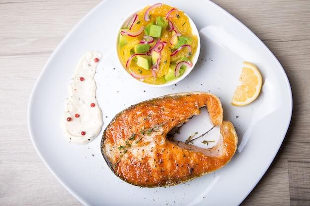 Salmão grelhado, salada com laranja e abacate.