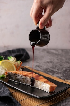 Salmão grelhado, sementes de gergelim e manjerona em um prato preto. fotografia de estúdio