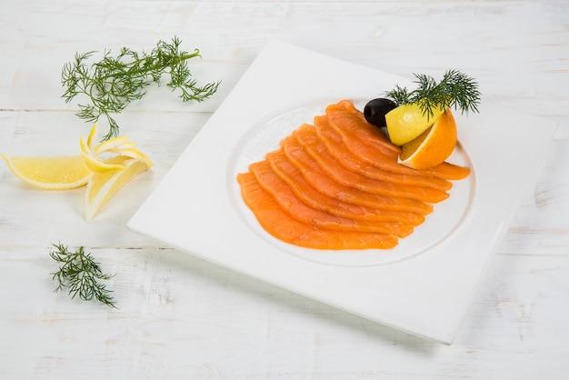 Salmão marinado com limão e laranja. decore com ervas. no fundo de madeira branco