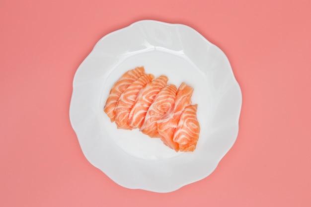 Salmão no prato no fundo rosa.