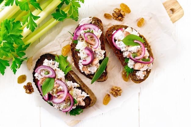 Salmão, pecíolo de aipo, passas, nozes, cebola roxa e salada de requeijão em pão torrado com alface verde em papel em um fundo de placa de madeira de cima
