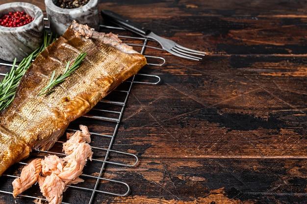 Salmão peixe fumado quente na grelha com ervas. fundo de madeira escuro. vista do topo. copie o espaço.