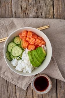 Salmão pique tigela com peixe fresco, arroz, pepino, abacate com gergelim preto e branco.