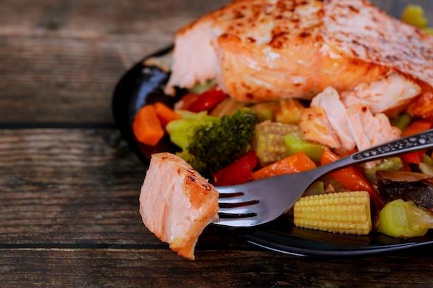 Salmão rosa frito saudável com legumes asiáticos no prato com garfo.