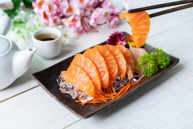 Salmão sashimi fatia fresco servir no gelo com chá, estilo japonês