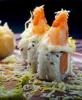 Salmão uramaki filadélfia com camarão e raspas de limão siciliano em um prato com textura oriental.