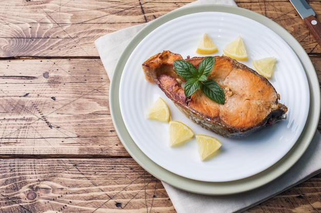 Salmões cozidos bife dos peixes em uma placa com limão. mesa de madeira.