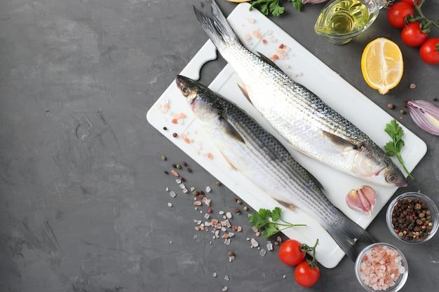 Salmonete de peixe cru com ingredientes e temperos na placa de plástico branca na mesa escura com lugar para texto. vista de cima
