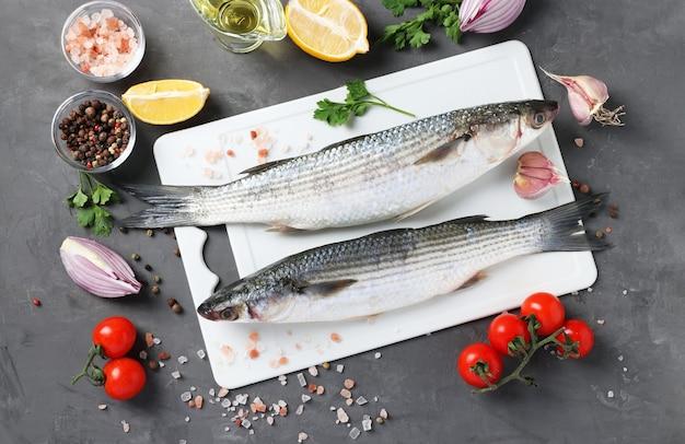 Salmonete de peixe cru com ingredientes e temperos na placa de plástico branca sobre fundo escuro. vista de cima