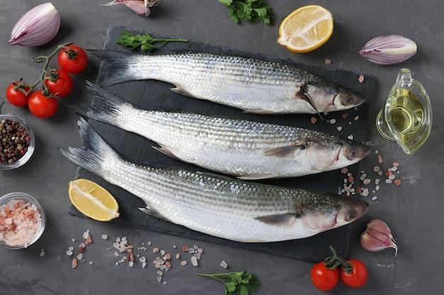 Salmonetes frescos prontos para cozinhar com ingredientes e temperos como salsa, limão, tomate cereja, cebola roxa e azeite de oliva em superfície escura. vista de cima.