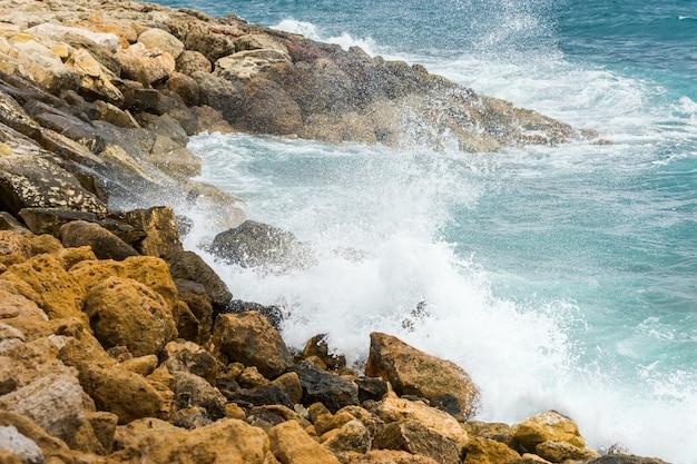 Salpicos de água do mar batendo nas rochas costeiras