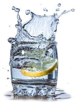 Salpicos de água, limão caindo em um copo