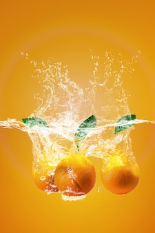 Salpicos de água na laranja e folhas de chá refrescantes de verão