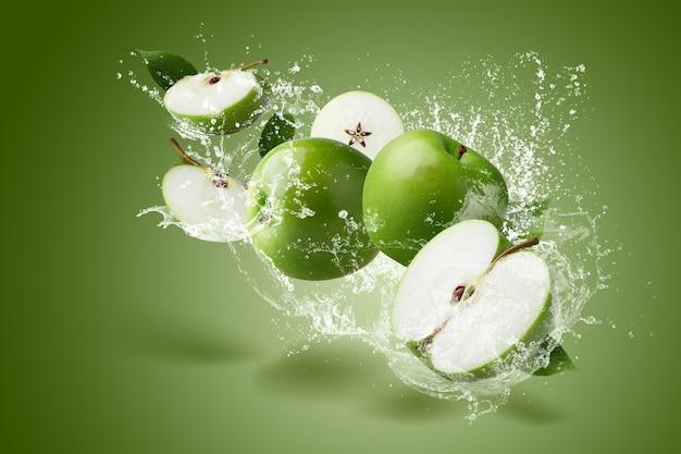 Salpicos de água na maçã verde com folha verde e corte a fatia com sementes sobre fundo verde.