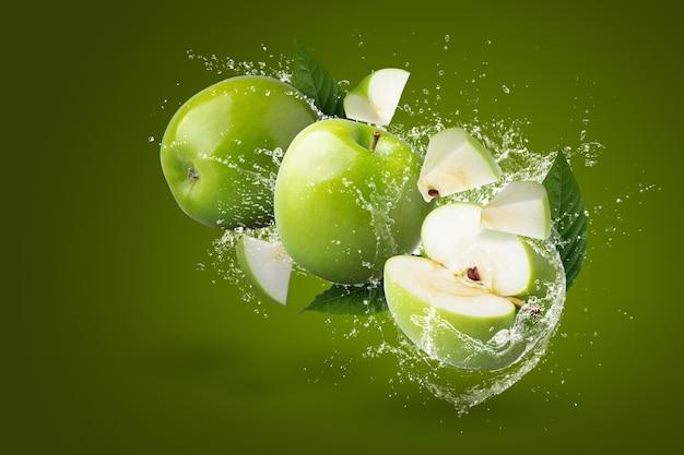 Salpicos de água na maçã verde isolada em um fundo verde.