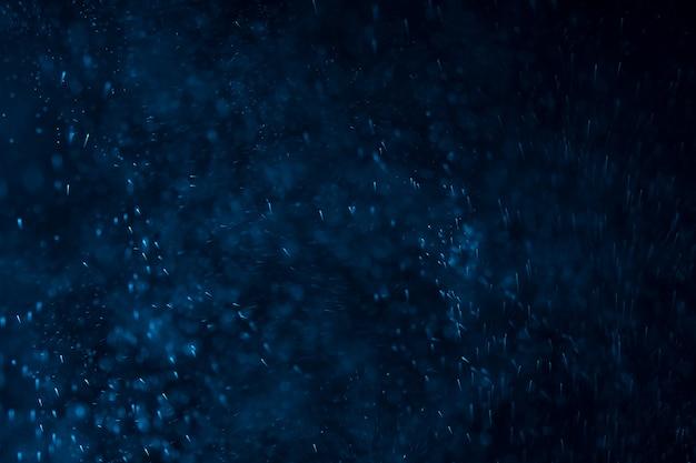 Salpicos de água ou neve em uma parede escura com uma tonalidade azul