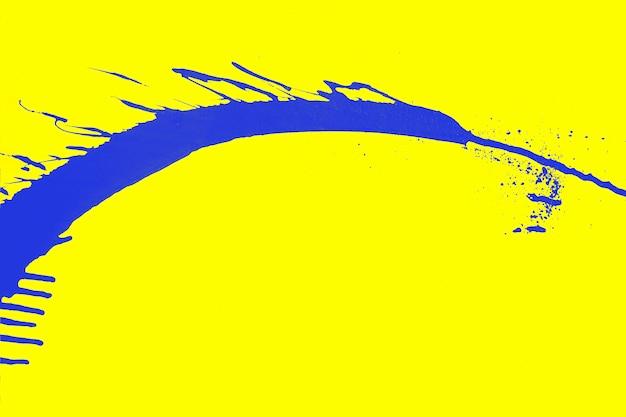 Salpicos de tinta azul abstrata, elemento de grafite criativo sobre um fundo amarelo brilhante.