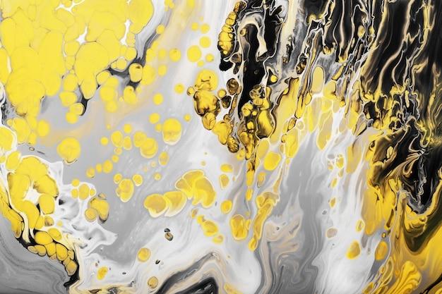 Salpicos de tinta preta e amarela e bolhas amarelas em fundo cinza. fundo ou textura do efeito de mármore. fluid art.