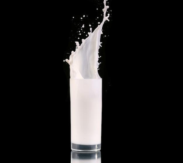 Salpicos em um copo com leite isolado no preto