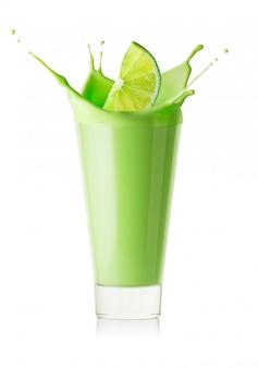 Salpicos no copo de smoothie verde ou iogurte da fatia de limão