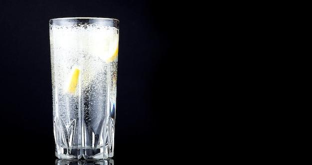 Salpique em um copo com limão em um fundo preto, copie o espaço