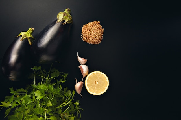Salsa, alho, limão, sementes de gergelim e duas berinjelas frescas isoladas no preto