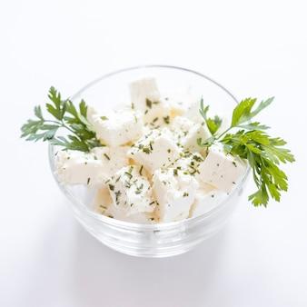 Salsa com cubos de queijo na taça de vidro contra um fundo branco