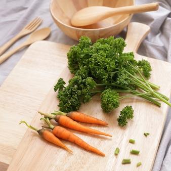 Salsa e cenoura no bloco de desbastamento de madeira