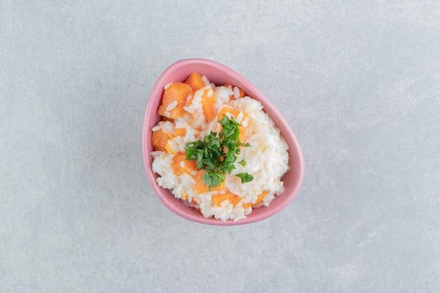 Salsa fatiada e arroz de cenoura na tigela, no fundo de mármore.
