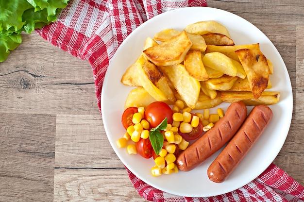 Salsicha com batatas fritas e legumes em um prato