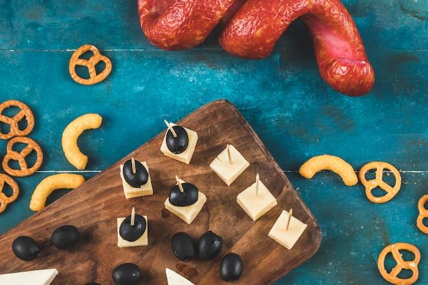 Salsicha com cubos de queijo, azeitonas e biscoitos em uma placa de madeira, vista superior