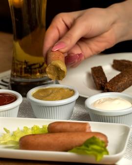 Salsicha com mostarda e um copo de cerveja